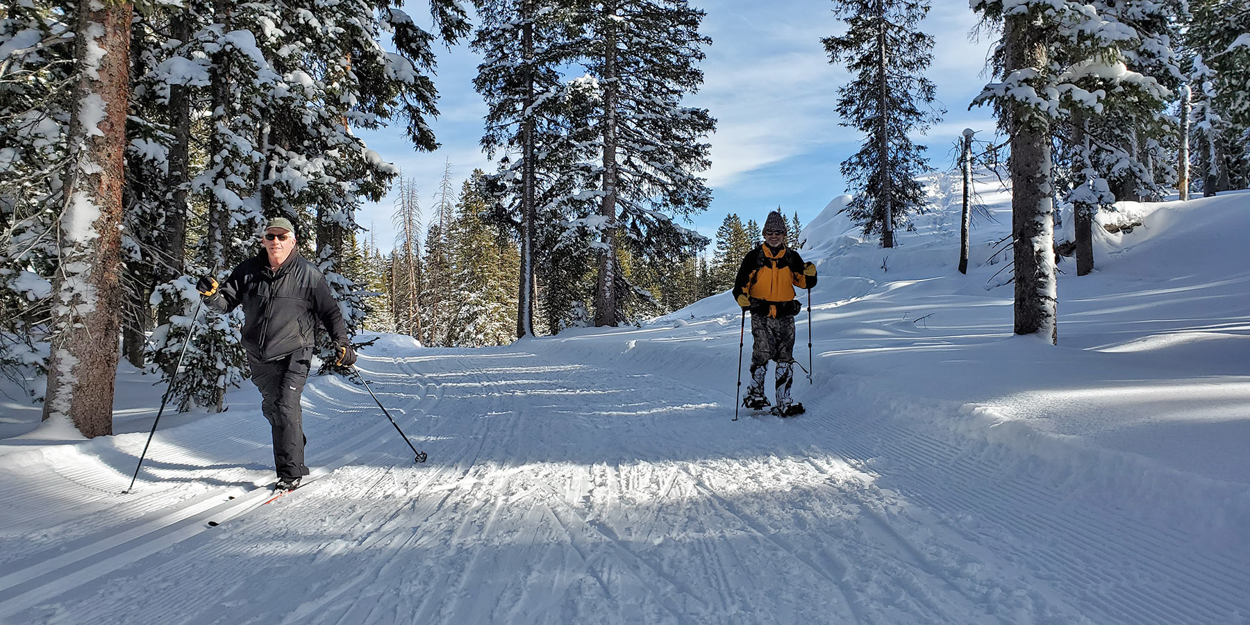 Snowshoer and cross country skier enjoying GMNC trails on Grand Mesa.